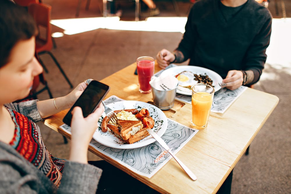 woman on phone during meal
